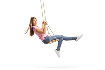 Young woman with long hair swinging on a wooden swing