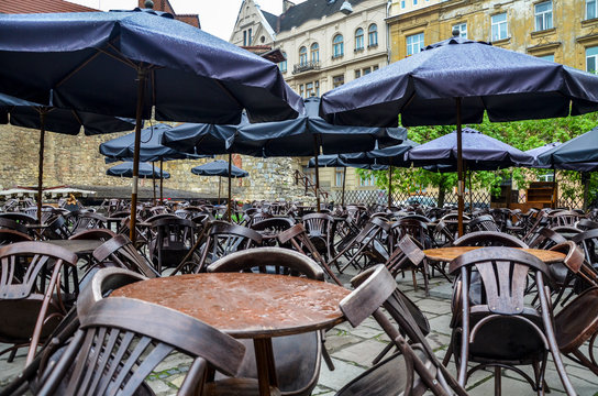 outdoor cafe with small round tables and wooden chairs table chair after rain at the cloudy day
