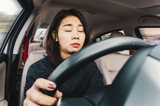 Tired Asian woman fall sleeping  while driving the car
