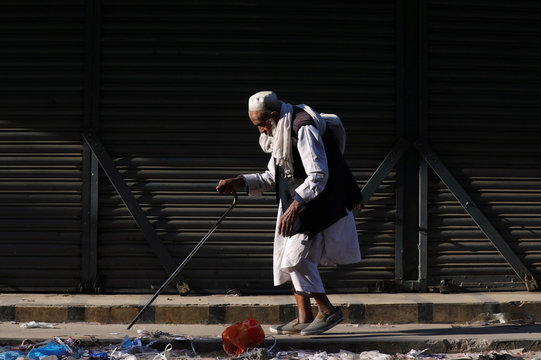 A man walks with the help of stick in the sunlight to warm himself on an early winter morning in Karachi,