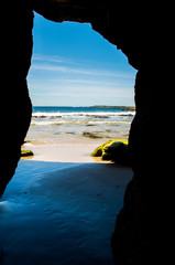 View to the ocean with the blue sky from the dark cave (Australia)
