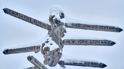 wooden signpost to capitals with snow