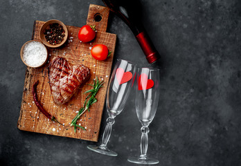 grilled beef steak in the form of a heart with spices and a bottle of champagne or wine with two glasses for dinner for Valentine's day on a stone background with copy space for your text