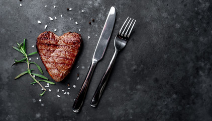 Photo sur Toile Steakhouse grilled beef steak in the form of a heart with spices, a knife and a fork for Valentine's Day on a stone background with copy space for your text