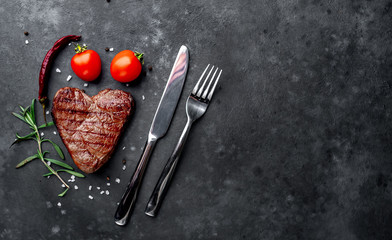 Photo sur Plexiglas Steakhouse grilled beef steak in the form of a heart with spices, a knife and a fork for Valentine's Day on a stone background with copy space for your text