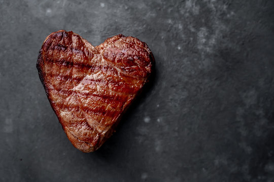 grilled beef steak in the form of a heart for Valentine's day on a stone background with copy space for your text