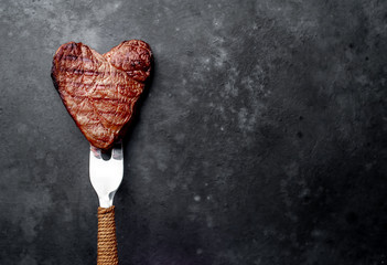 Photo sur Plexiglas Steakhouse grilled beef steak in the form of a heart on a fork for Valentine's day on a stone background with copy space for your text
