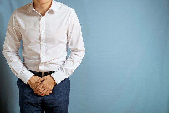 A man in trousers and a white shirt holds on to his groin, a symbol of testicular cancer