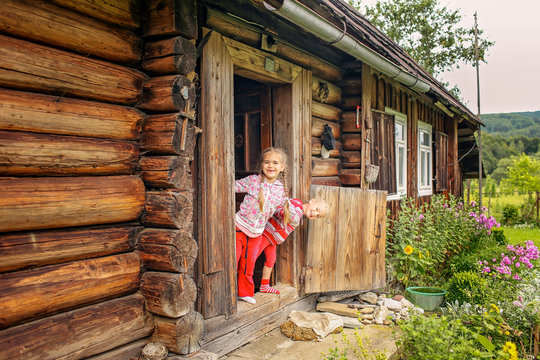Children having rest on the doorstep of old wooden house during summer vacation, eco-friendly travel concept