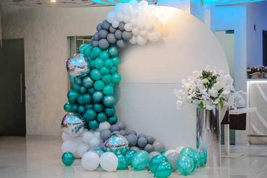close up photo of a white round photo zone with turquoise and gray baloons at a boy's birthday party in a restaurant