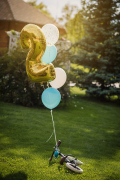 close up photo of a birthday present for a 2-year boy: a bike with balloons laying on the grass