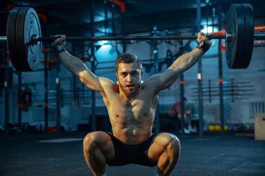 Caucasian man practicing in weightlifting in gym. Caucasian male sportive model training with barbell, looks confident and strong. Body building, healthy lifestyle, movement, activity, action concept.