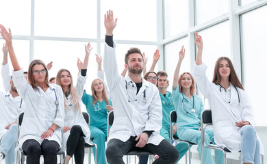 medical students raising their hands during the seminar.