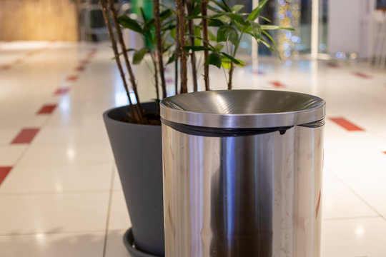 close-up steel cylinder bin litter bin. near in blur a plant in a gray tub. Against the background of a light floor tile and the interior of a public place in blur