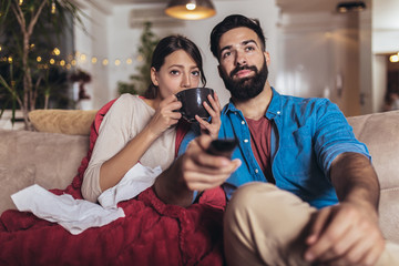 Cheerful romantic couple is sitting on sofa under cozy plaid and smiling. They are drinking tea and watching tv.