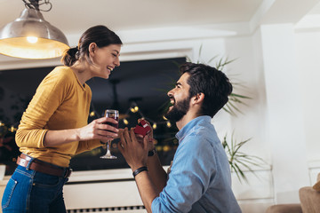 Happy man giving engagement ring in little red box to woman at home