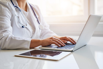 Female doctor typing on her laptop computer in medical office
