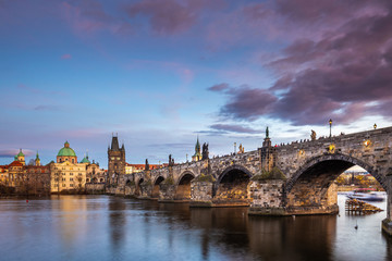 Foto op Aluminium Praag Prague, Czech Republic - Beautiful purple sunset and sky at the world famous Charles Bridge (Karluv most) and St. Francis Of Assisi Church on a winter afternoon