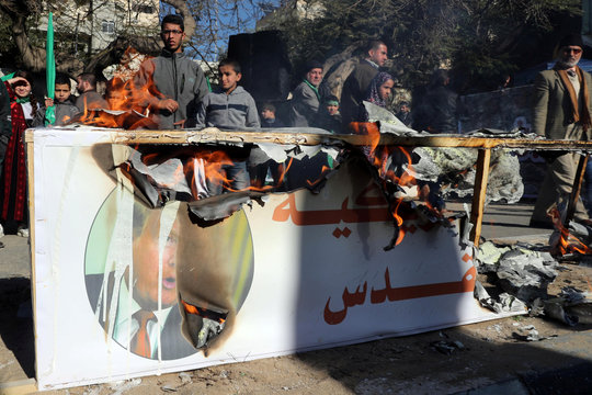 Palestinian Hamas supporters burn a model of a coffin representing the U.S. embassy in Jerusalem with a picture of U.S. President Donald Trump, during a rally in Gaza