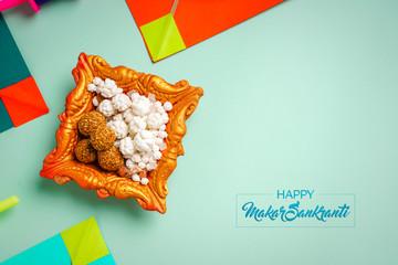 Makar Sankranti festival Concept, Colorful paper kites and string , Sesame seed ball or til ke...