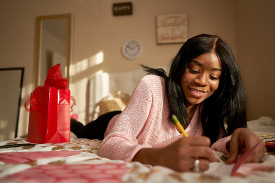 pretty african american woman writing love letter for valentines day on bed