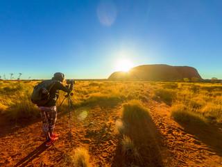Uluru Ayers Rock photographer silhouette at sunrise. Photographer woman taking pictures with tripod in Uluru-Kata Tjuta National Park. Sun rays in Australian outback. Northern Territory, Australia.