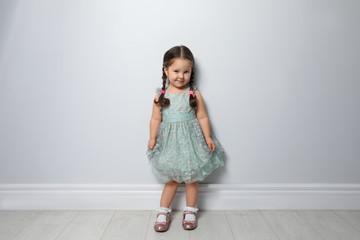 Cute little girl near light grey wall Fototapete