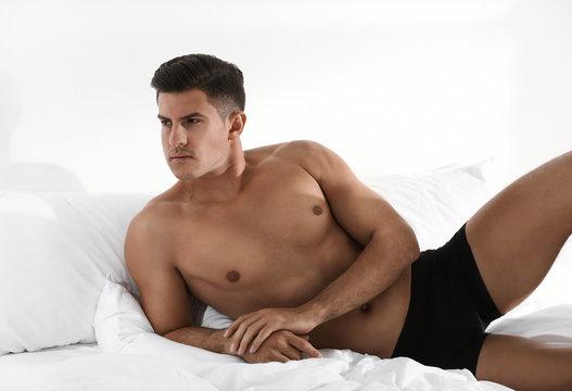 Handsome man in black underwear on bed indoors