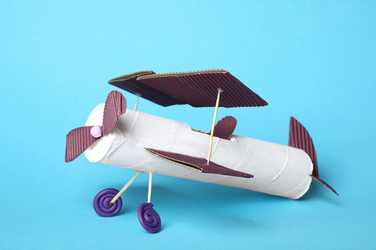 Toy plane made of toilet paper hub on light blue background