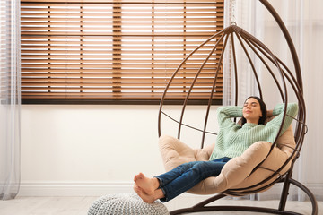 Young woman relaxing in hanging chair near window at home. Space for text