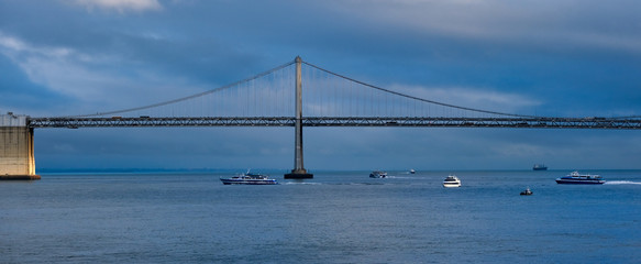 Fototapete - Boats Under Bay Bridge on a Stormy Blue Day