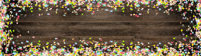 Deurstickers Carnaval Carnival background panorama banner long - Frame made of colorful confetti isolated on brown wooden texture, top view with space for text