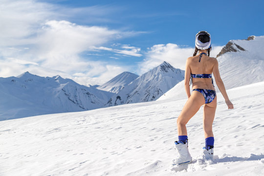 Woman wearing bikini standing on snow mountain top in ski resort. Beautiful mountains view background.