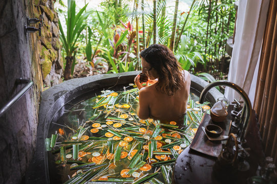 Young woman enjoying in outdoor luxury spa. Beautiful luxury stone bath tub with jungle view.Natural organic tropical ingredients in the water:ginger,lime,orange and sea salt. Beauty treatment concept