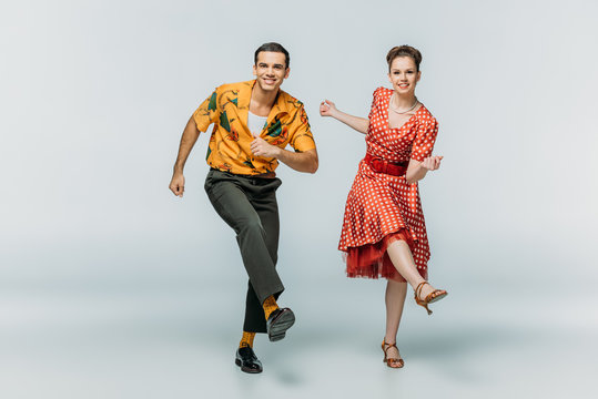 stylish couple looking at camera while dancing boogie-woogie on grey background