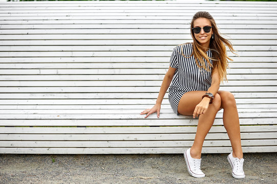 Stylish beautiful girl sitting on a bench