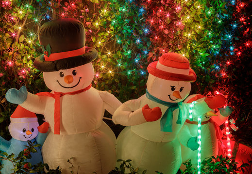 Snowman Family decorating front yard at night. Palo Alto, California, USA.
