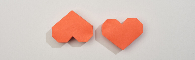 Top view of red paper hearts on grey background, panoramic shot