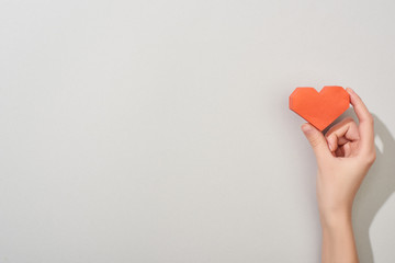 Top view of girl holding paper heart on grey background with copy space