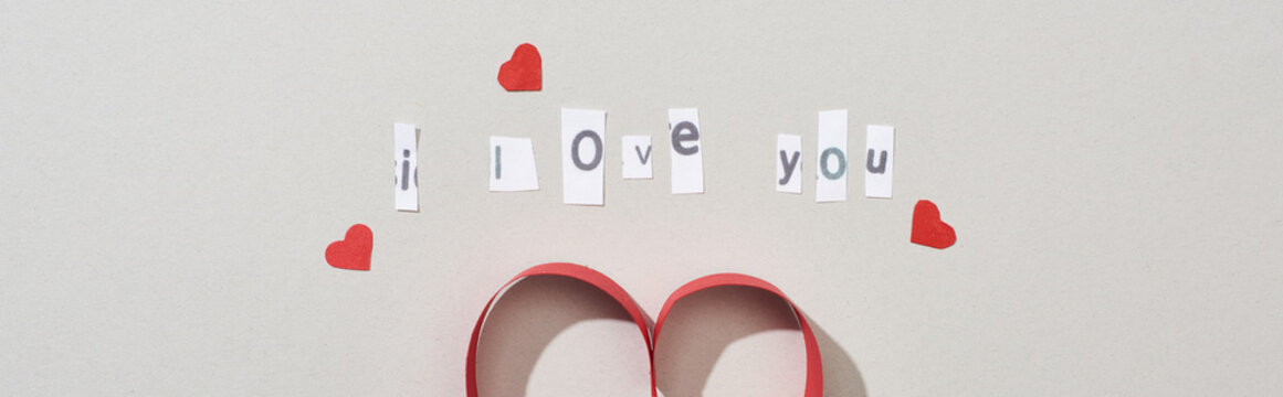 Top view of i love you lettering with paper hearts on grey background, panoramic shot