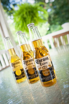 Woodbridge, New Jersey - September 21, 2013: Corona Mexican beers sit on a glass patio table.  You can see greenery in the background
