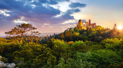 Sintra, Portugal. National park with Palace of Pena. Sunrise among green trees of forest with...