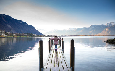 Foto op Aluminium Meer / Vijver A trip photo of a young girl standing on the old wooden bridge happily in the natural scenery on the river in the lake next to the mountain in the morning.