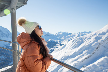 A picture of a beautiful woman looking at a mountain with a lot of snow happily as a holiday vacation and enjoying nature in the mountains. The famous GRINDELWALD-FIRST of Switzerland.