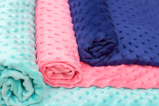 plush fabric with pimples. pink, turquoise, blue colors. background texture of plush fabric. studio shop