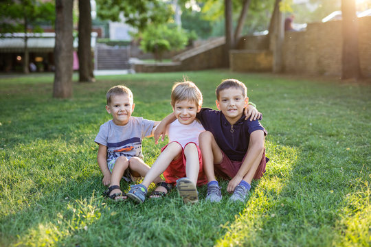 Three happy young boys in summer park