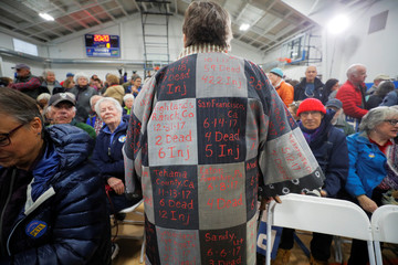 An audience member wears a coat decorated with the statistics from mass shootings in North Conway