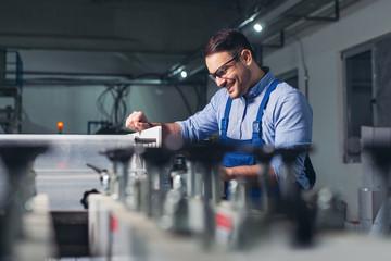 Modern industrial machine operator working in factory. Worker on the machine