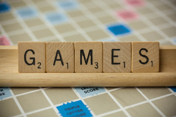 WOODBRIDGE, NEW JERSEY - November 9, 2018: Scrabble tiles spell out the word games on a vintage game board