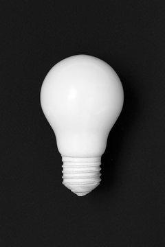Lightbulb painted in white matte paint on black background